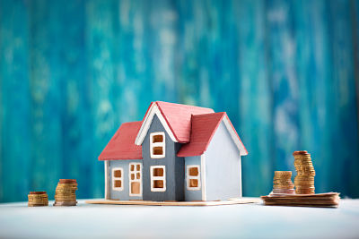 Red house model on wooden background with banknotes and coins