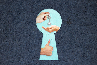 Keyhole with hands on concrete background to illustrate illegal sub-letting