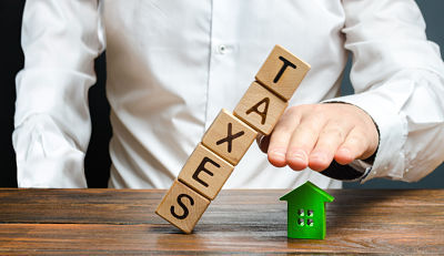 A man protects his hand with a figurine of a house from a falling tower of cubes with the word taxes.