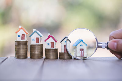 House searching concept with a magnifying glass, house and money. magnifying glass and coins. concept of mortgage, construction, rental housing.