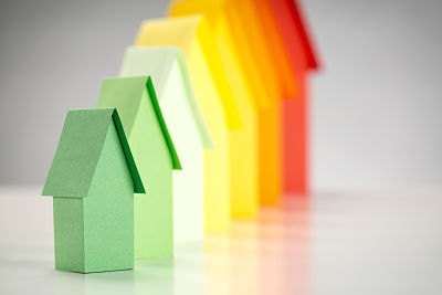 Paper houses in energy label colors, focus on the most efficient green house.