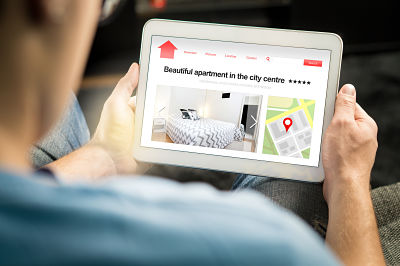 Hands holding a tablet on which is a property listing website