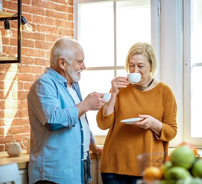 Senior couple having a coffee time, standing together near the window on the kitchen at home