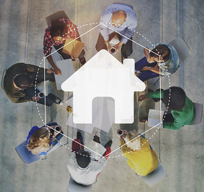 A group of people connected around the image of a house.