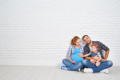 Happy family father and pregnant mother and child daughter near a blank brick wall in the room