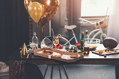 Messy table with pizza in box and beverages at morning after party