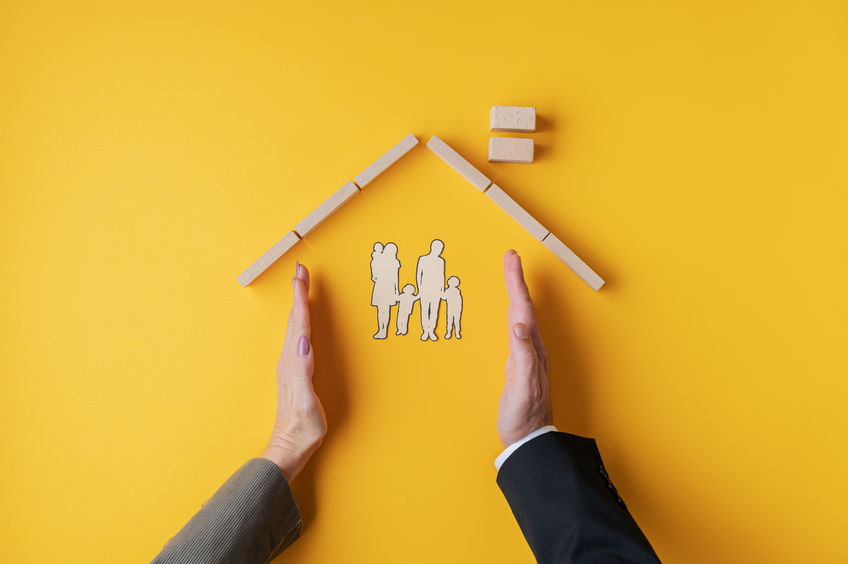 Male and female hands placed to form a home for paper cut silhouette of a family in a conceptual image. Over yellow background.