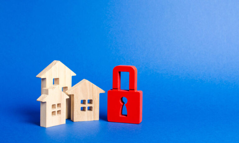 Three houses and a red padlock. Unavailable and expensive real estate. house Insurance. Security and safety. Confiscation for debts. alarm system. seizure of property. Protection of property rights.