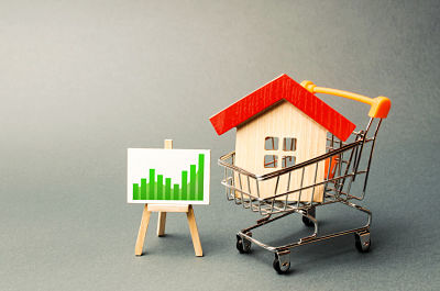 A red roof house in a trading cart and a positive trend chart on a stand. Increasing cost and liquidity of real estate. Attractive investing. rising prices or renting. boom in the real estate market