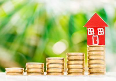 Red home model put on golden coins with fresh green nature background, saving to buy house concept