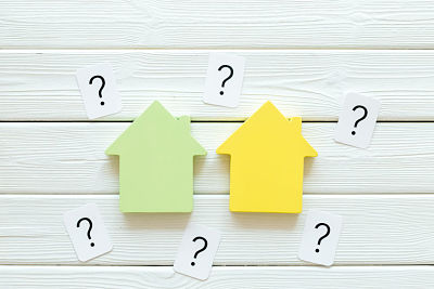 Purchasing a new property on credit. Mortgage credit concept with house toy and question mark on white wooden background top view space for text