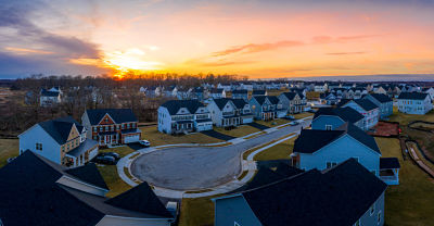 Curving suburban neighborhood dead end street with newly constructed single family homes in an American residential real estate development with stunning orange, pink, red, blue, yellow sunset