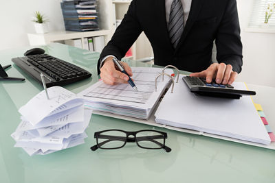 Close-up Of Businessman Calculating Tax In Office