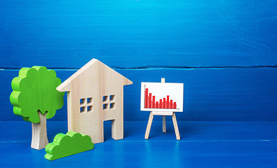 Residential building and easel with red falling trend chart. Fall of the real estate market, reduction of prices and low demand for housing. Lower mortgage interest rates. Bad economy
