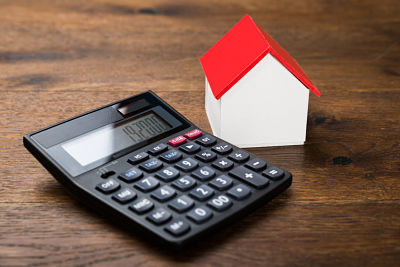 Close-up Of Miniature House With Calculator On Wooden Table