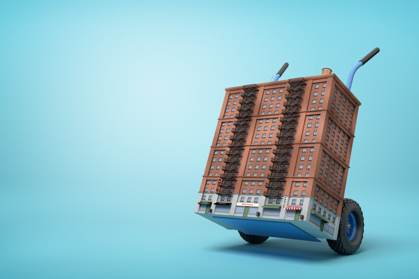 3d rendering of small 16-storeyed block of flats on blue hand truck on light-blue background. Flats for sale. Solve housing problem. City redesign.