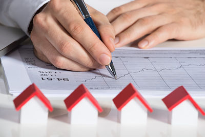 Cropped image of businessman preparing financial chart with house models at office desk