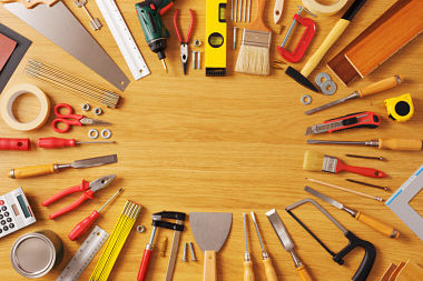 DIY and home improvement banner with work and construction tools on a wooden workbench top view, copy space at center
