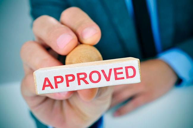 Rubber stamp saying approved to indicate mortgage acceptance